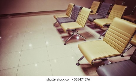 Rows of leather seats with metal legs in warm vintage lighting style
