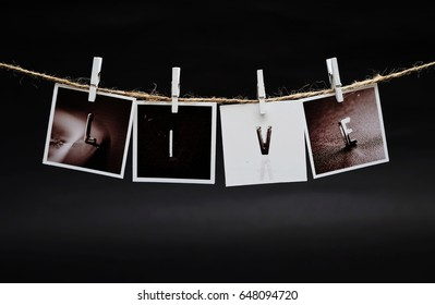 Rows of LIVE photo frames hanging with clothespins on dark background