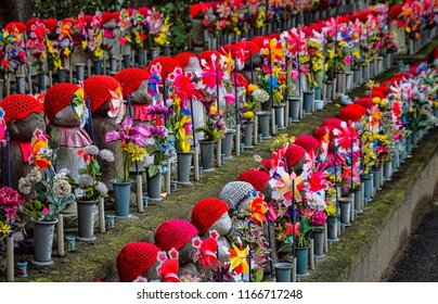Rows of Many Buddhist Jizo Statues with Red Bibs, Hats, Scarves, and Fans. Religious Stone Children Statues (Tokyo, Japan).