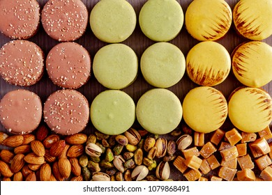 Rows of many pistachio, almond and salted caramel macarons with fresh almonds, pistachios and salted caramel pieces