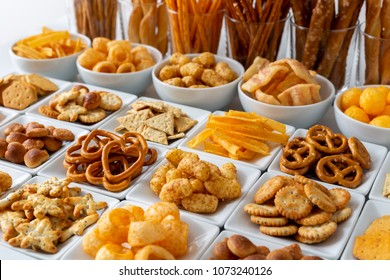 Rows of many types of savory snacks in white ceramic dishes.