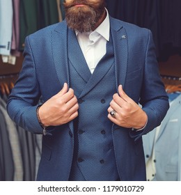 Rows of men suit jackets on hangers. Bearded man in suit. fashion and beauty, business and office wear, youth, muscular and healthy, shopping and wardrobe, boss and employee, man in shirt, copy space