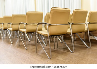 Rows of metal chairs at the conference in an empty room. Back view