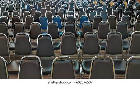 Rows of metal chairs at the conference in an empty room. front view