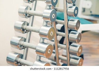 Rows of metal heavy dumbbells on stand in sport gym, physiotherapy clinic. Physical therapy center. Sports equipment for training. Selective focus. copy space.