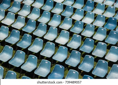 Rows of numbered uniform plastic chairs prepared for an event outdoors