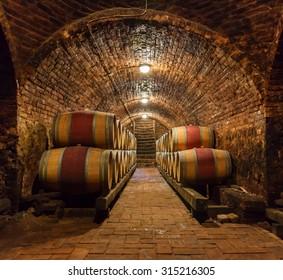 Rows of oak barrels in underground wine cellar