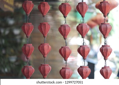 Rows of old electric garlands with lamps under the cloth shades on the wire frame ceiling. Vietnam