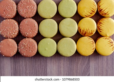 Rows of pistachio, almond and salted caramel macarons sitting on brown wooden table in natural light