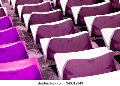 Rows of plastic chairs in a football stadium.