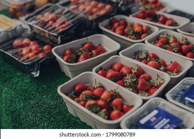 Rows of punnets with fresh strawberries on sale at a local market in the Cotswolds, UK.