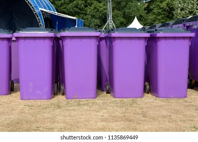Rows of purple plastic wheelie bins at festival