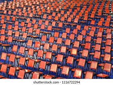 Rows of red chairs are set up for a public event