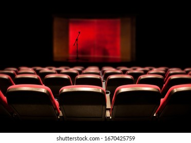 Rows of red empty chairs in front of stage with microphone on stand