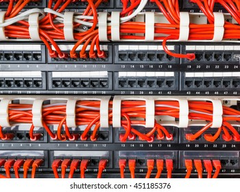 Rows of red network cables connected to router and switch hub in server room at internet data center