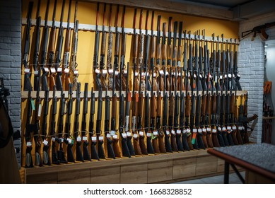 Rows of rifles on the wall, showcase in gun shop