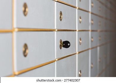 Rows of safety deposit boxes in a bank vault or security lockers with a receding perspective and a key in the lock of one of the doors