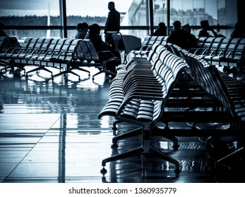 Rows of shairs at a departure lounge of a modern airport