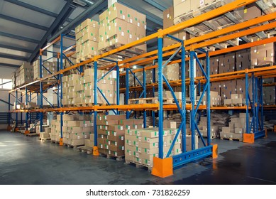 Rows of shelves with boxes in big modern warehouse