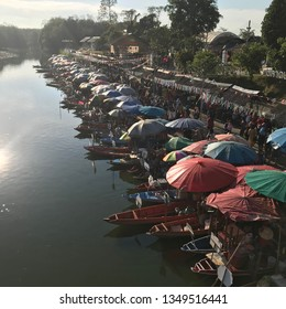Rows of small boats or sampan with umbrellas lining up the river for morning river market in early morning