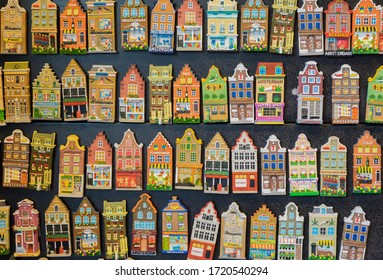 rows of small colourful cute Amsterdam's houses magnets on black board. Souvenirs of Amsterdam