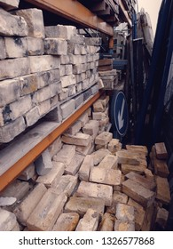 Rows of soft bricks and road maintenance hardware at a salvage yard in the UK.