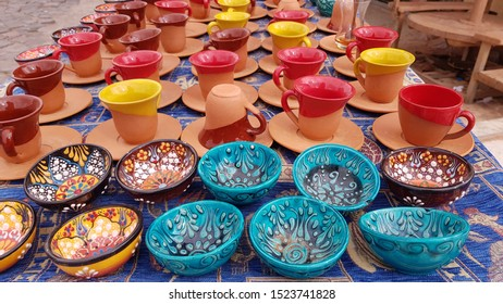 Rows of souvenir ceramic ornate bowls and colorful cups on Turkish bazaar in Cappadocia Turkey. Colorful craft ceramic kitchen utensils. Pottery textures.