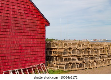 Rows of staked lobster traps, behind a brightly painted red shingled building,  waiting for the lobster season to begin, a part of the maritime fishing industry, in Prince Edward Island Canada