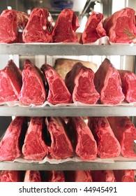 Rows of steak on metal racks in refrigerator.  Vertical shot.