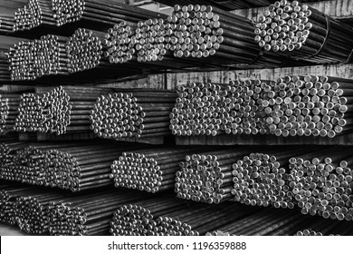 Rows of Steel Round Bar storage and stacking in the warehouse for industrial construction. Black and white with Shallow focus.