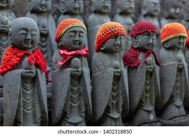 Rows of stone Buddhas. Many stone sculptures of the Buddha in red knitted hats. Buddha figures of Hase-Dera Temple in Kamakura, Japan. Jizo statues at Jizo-Do