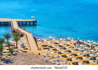 The rows of straw sunshades on the cozy sand beach, located on shore of El Maya bay in Sharm El Sheikh, Egypt.