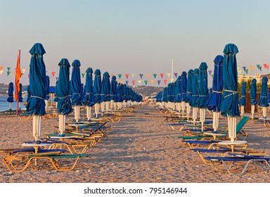 Rows of sun loungers and parasols on the beach at sunrise