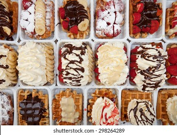 Rows of take away street waffles topped with strawberries, chocolates and whipped cream in Brussels of Belgium.
