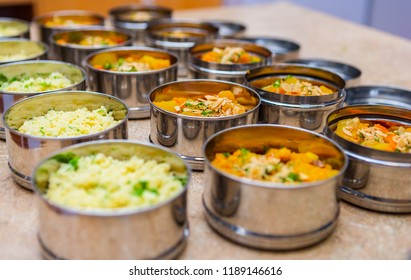 Rows of Tiffin (Dabba) Meal Box Containers Filled with Herbed Couscous and Vegetable Stew