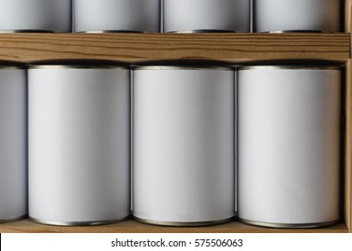 Rows of tin cans with unbranded, blank white labels, on wooden shelves.