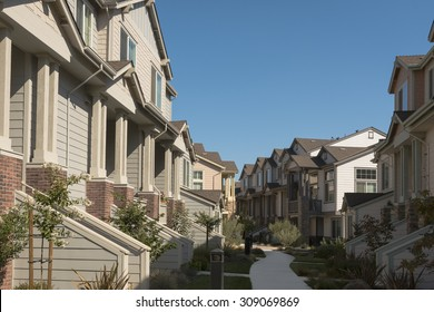 Rows of townhomes facing each other with a concrete path down the middle.