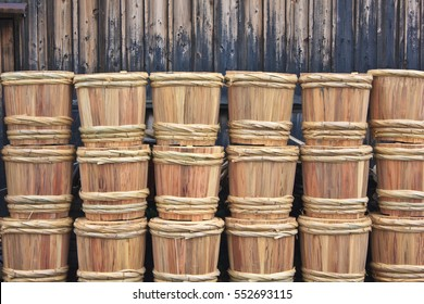 Rows of traditional wooden sake barrels with bamboo hoops wait on the street behind a sake brewing factory warehouse in Japan.