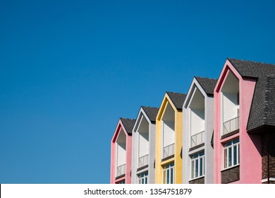 Rows of triangular parts of roofline covered with shingle, colorful pink and yellow house against blue sky. Copy space