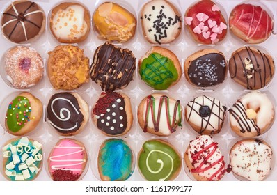 Rows of various delicious doughnuts in a box