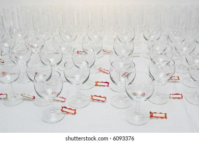 Rows of water glasses with name tags, on a linen tablecloth