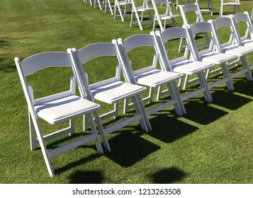 Rows of white chairs on a lawn