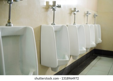 Rows of white and clean urinals for men.