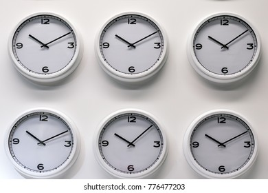 Rows of white plastic wall watches on the white background