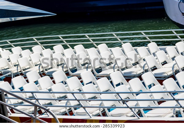 Rows of white seats on the open deck of a ferry