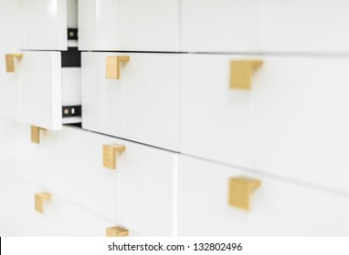 Rows of white sleek drawers with golden handles in strict geometric style. Two half-opened drawers in background. House or office interior. Furniture and keeping things.