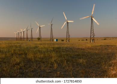 Rows of wind turbines at sunset. Green energy generation. Yevpatoriya, Crimea.