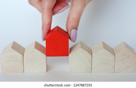 Rows of wooden houses with single red house on white background