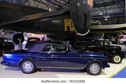 Royal Air Force Museum, London, UK - 12/08/15: 1990 Bentley Continental convertible beneath Avro Lancaster 1, with 1938 Studebaker Commander sedan behind, for Bonhams Classic Car Auction.