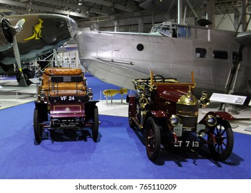 Royal Air Force Museum, London, UK - 12/08/15: 1901 De Dion Bouton 4½HP Type and 1913 Morris Oxford 9.9HP 'Bullnose' two-seat tourer in front of Supermarine Stranraer, for Bonhams Classic Car Auction.